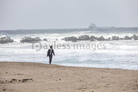 波打ち際を歩くビジネスマンの写真イラスト素材 Gf1420773083